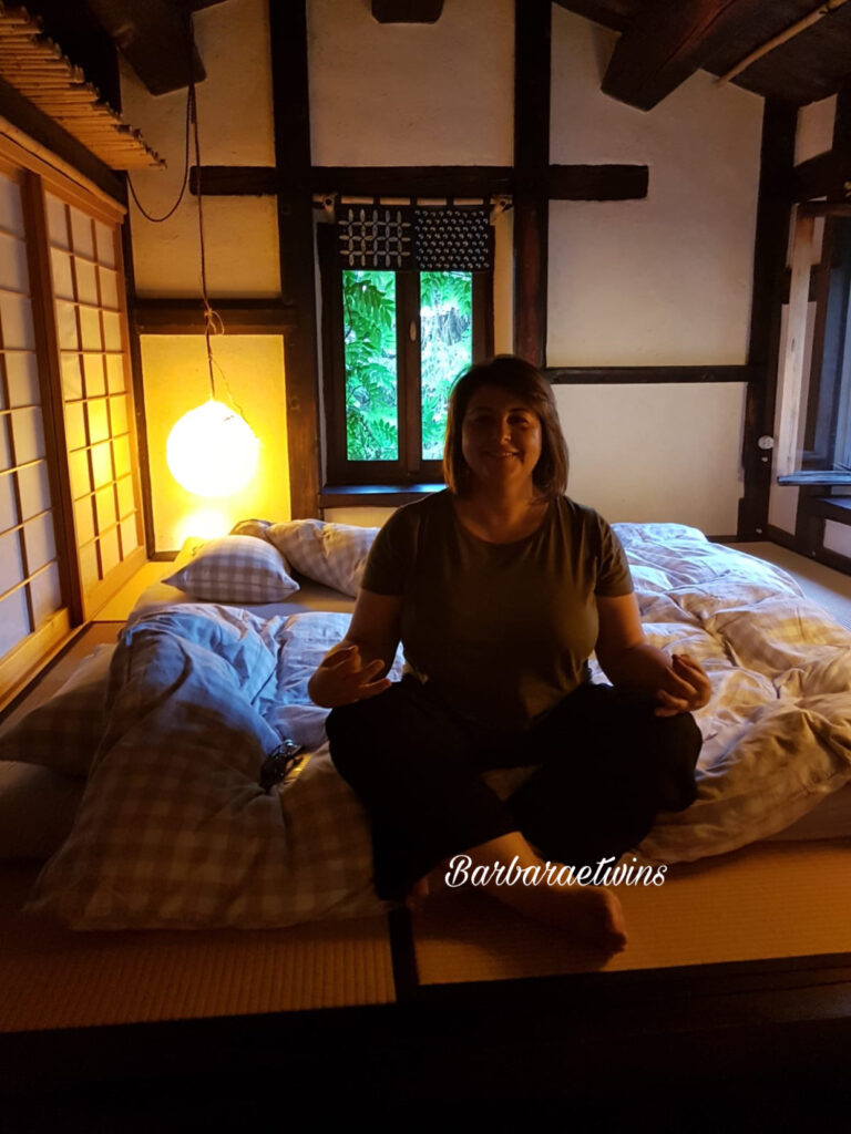 donna in camera giapponese con tatami e futon dove dormire in Italia