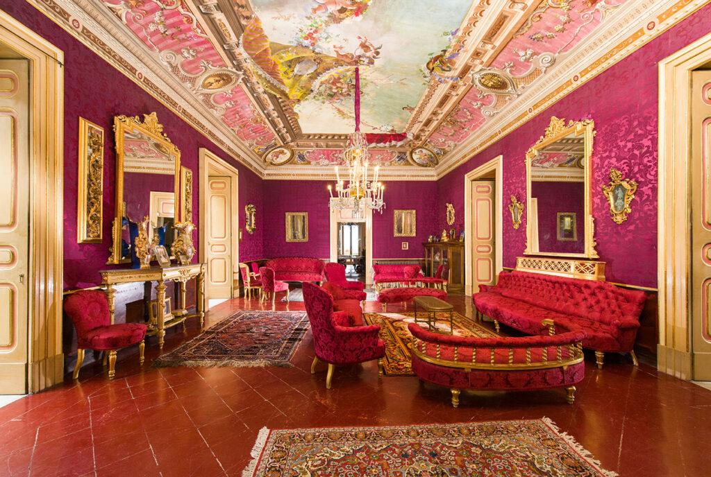 salone rosso con specchi, divani d'epoca dove dormire in Italia
