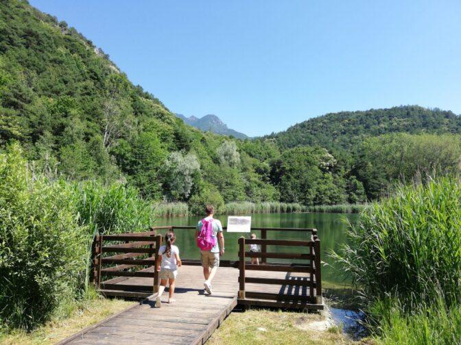 lago con pontile con un due bambini e un adulto dove dormire in Italia