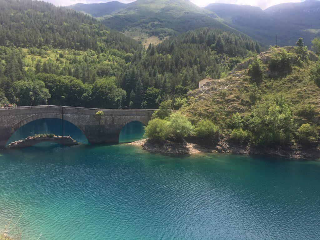 ponte sul lago con montagne