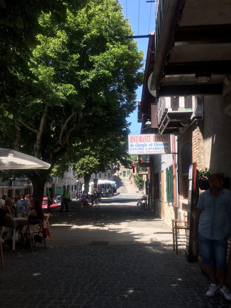 ingresso ristorante con insegna e tavolini e strada