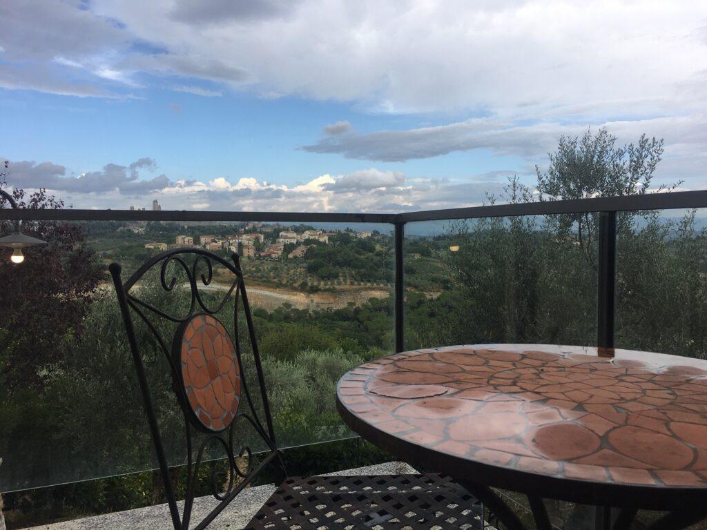tavoli e sfondo e sedia su balcone paesaggio san gimignano